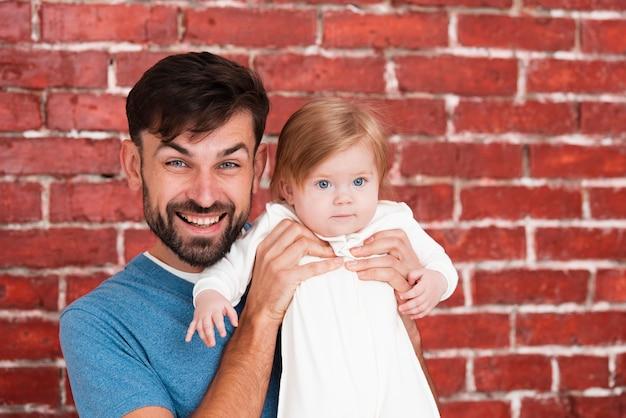 Vater, der baby mit ziegelsteinhintergrund hält