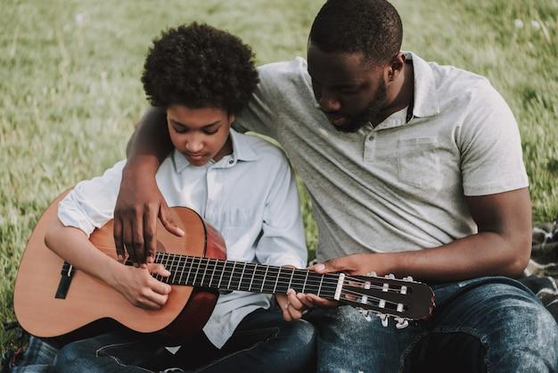 Vater, der dem sohn lektionen zeigt, um auf gitarre zu spielen