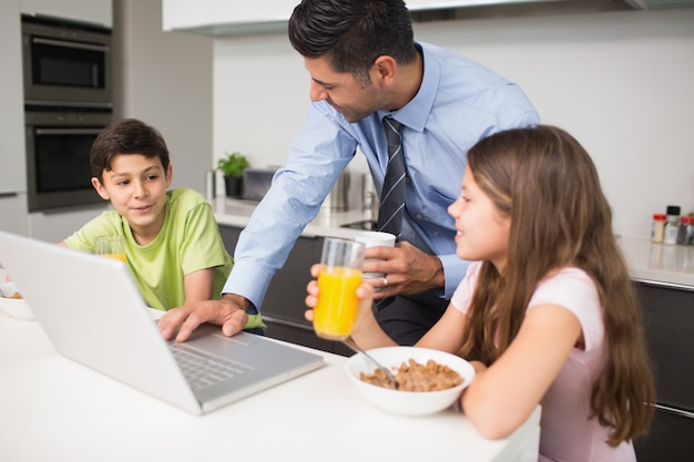Vater, der den laptop und kinder frühstückt in der küche verwendet