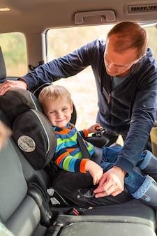 Vater, der den sicherheitsgurt für seinen kleinen jungen in seinem autositz anschnallt. sicherheit des kinderautositzes