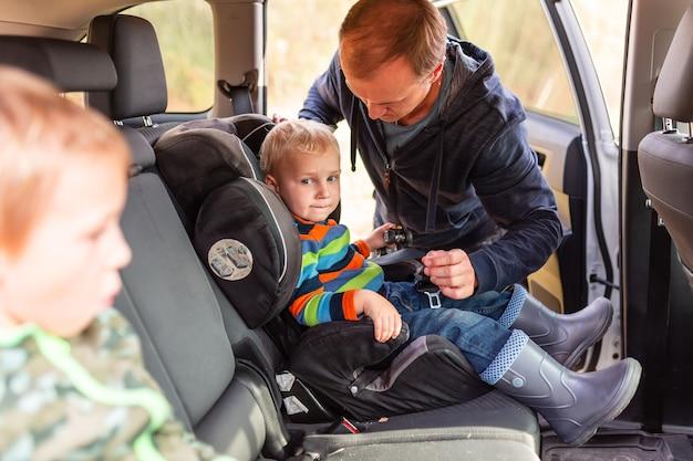 Vater, der den sicherheitsgurt für seinen kleinen jungen in seinem autositz anschnallt.