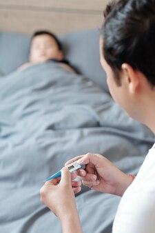 Vater, der ein elektronisches thermometer verwendet, wenn er die temperatur seines an grippe erkrankten kindes überprüft