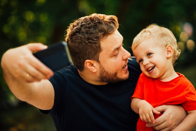 Vater, der ein selfie nimmt und sein kind betrachtet