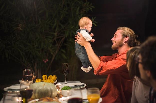 Vater, der kleines baby auf familienabendessen hält
