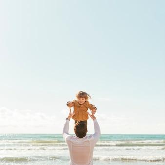 Vater, der lachendes kleinkind oben im himmel wirft