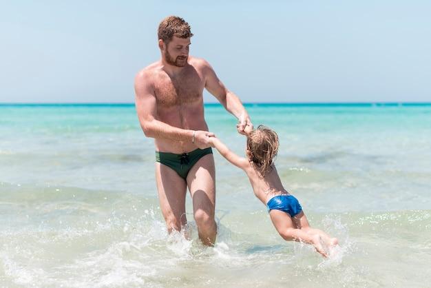 Vater, der mit kind im meer spielt