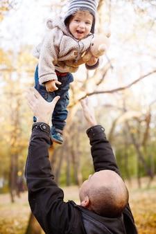 Vater, der mit sohn im herbst-park spielt