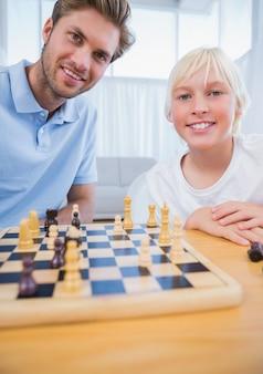 Vater, der schach mit seinem kleinen jungen spielt