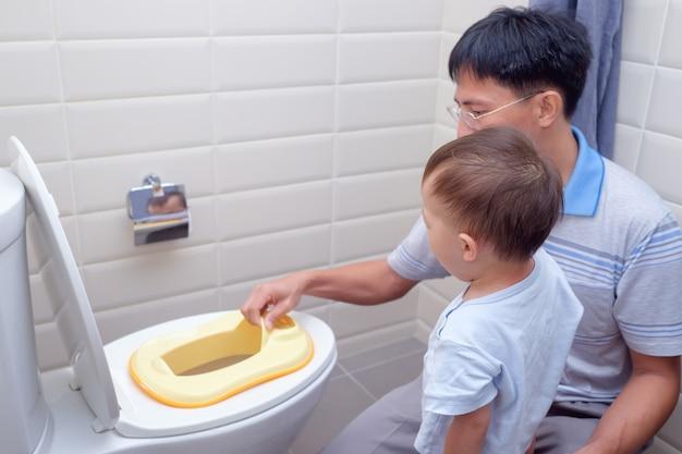 Vater, der schläfrigen sohn trainiert, um toilette im badezimmer zu benutzen, asiatischer kleinkindjunge, der auf toilette mit kinderbadezimmerzubehör sitzt