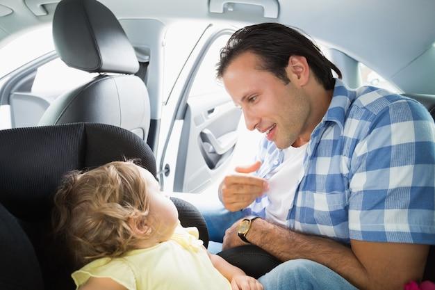 Vater, der sein baby im autositz sichert
