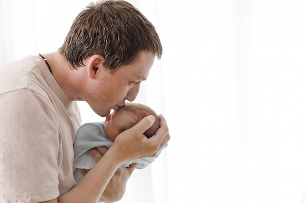 Vater, der sein neugeborenes kind umarmt und küsst