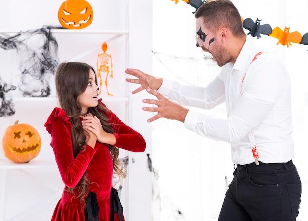 Vater, der seine tochter für halloween erschrickt