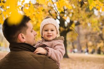 Vater, der Tochter in den Händen im Herbstpark hält