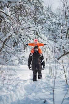 Vater, der tochter reitet, reitet zurück in den schneewald.