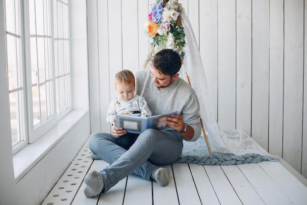 Vater, der zu hause mit kleinem sohn sitzt