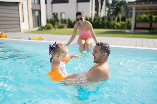 Vater fühlt sich glücklich. hübscher liebevoller vater, der sich glücklich fühlt, während er mit seinem süßen, reizenden mädchen schwimmt