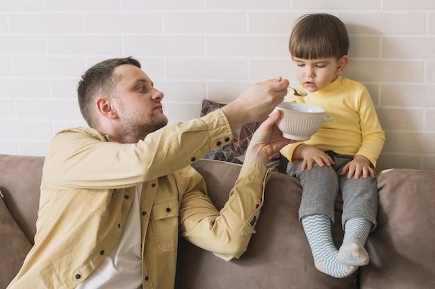 Vater füttert seinen sohn im wohnzimmer