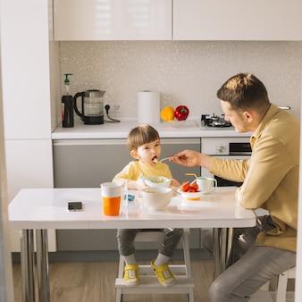 Vater füttert seinen sohn in der küche