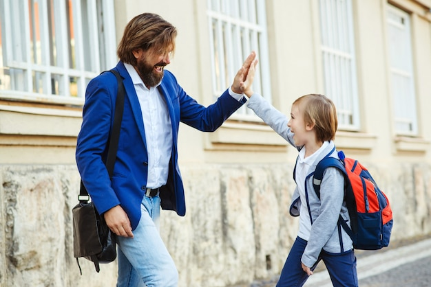 Vater gibt dem sohn high five, während er sich nach der schule trifft. vater gratuliert dem schüler zum erfolg in der schule.