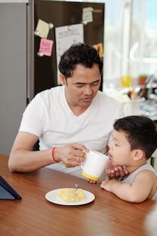 Vater gibt seinem kleinen sohn eine tasse wasser, wenn sie frühstücken und einen animationsfilm auf einem tablet-computer ansehen