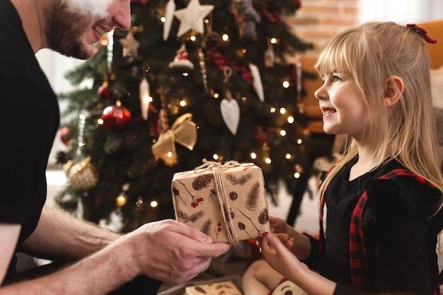 Vater gibt seiner lächelnden glücklichen tochter ein neujahrs- oder weihnachtsgeschenk oder ein geschenk