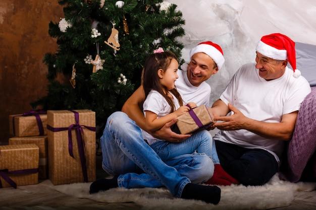 Vater, großvater und überraschte enkelin nahe dem weihnachtsbaum