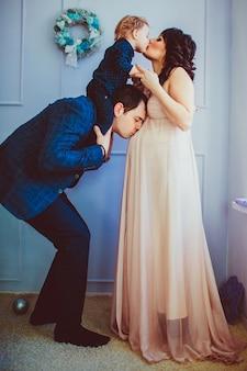 Vater hält an seinem hals kleinen sohn und küsst frau schwanger