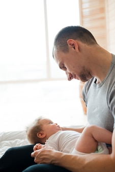 Vater hält baby auf den knien