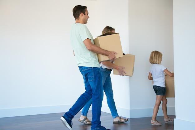 Vater hält pappkarton und geht nach frau und tochter zum korridor