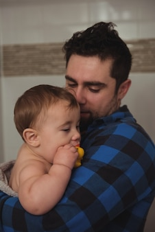 Vater hält sein baby im badezimmer