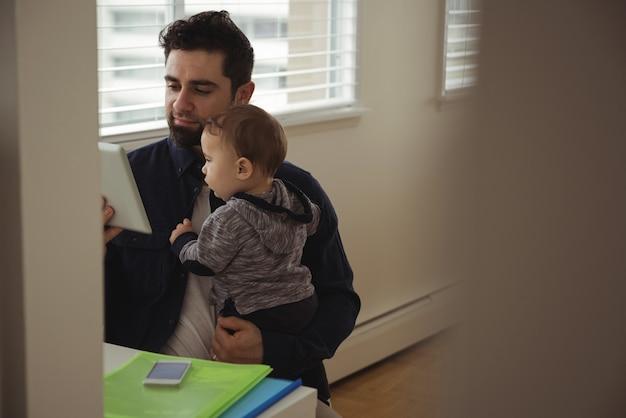 Vater hält sein baby, während er digitales tablett am schreibtisch benutzt