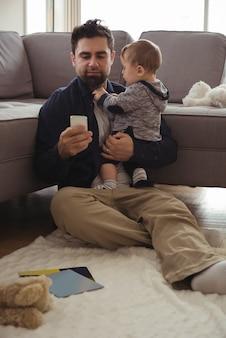 Vater hält sein baby, während er handy benutzt