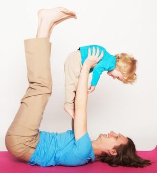 Vater hält seinen kleinen sohn auf den füßen, yoga, glückliche familie