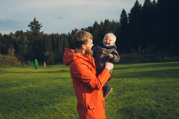 Vater halt kleinen sohn. glückliche familie, die in waldwiese geht. emotionales porträt des lebensstils draußen.