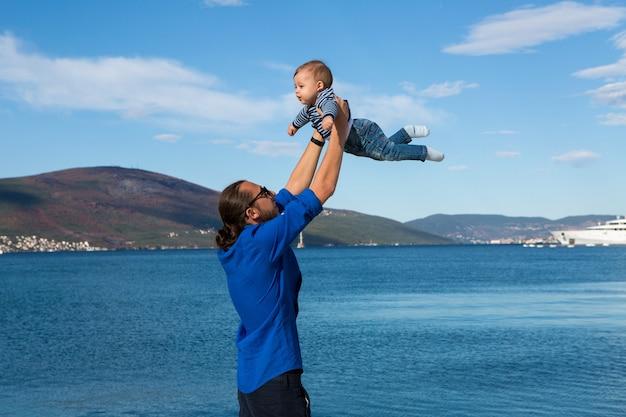 Vater hebt seinen sohn in seinen armen zum meer