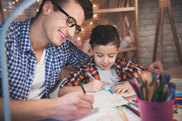 Vater hilft dem sohn, nachts zu hause mit buntstiften und markern auf papier zu zeichnen.