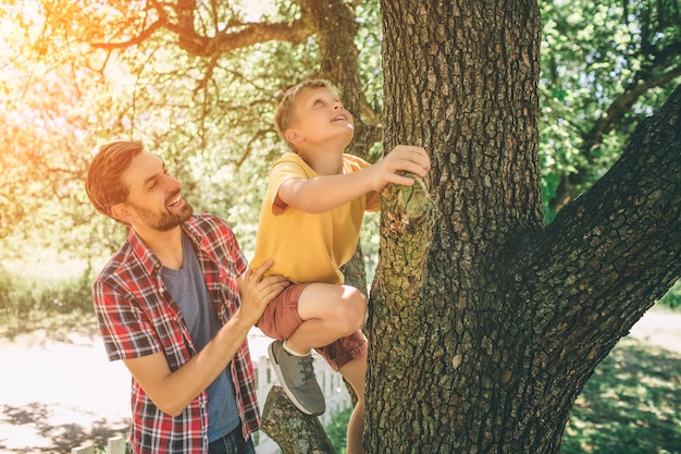 Vater hilft seinem sohn, auf den baum zu klettern
