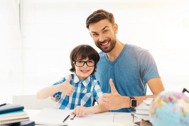 Vater hilft seinem sohn, hausaufgaben in der schule zu machen.