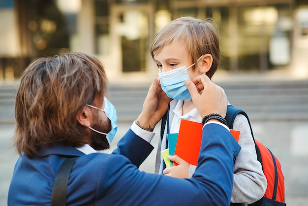 Vater hilft sohn und setzt gesichtsschutzmaske auf.