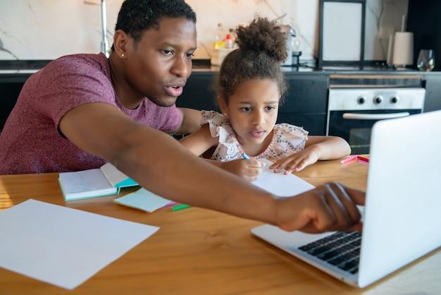 Vater hilft und unterstützt seine tochter bei der online-schule, während er zu hause bleibt. neues normales lifestyle-konzept.