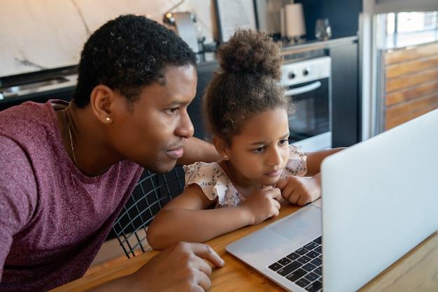 Vater hilft und unterstützt seine tochter bei der online-schule, während er zu hause bleibt.