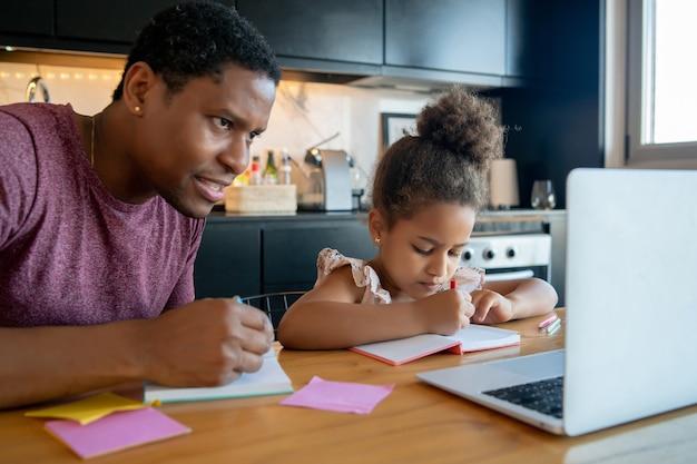 Vater hilft und unterstützt seine tochter bei der online-schule, während er zu hause bleibt