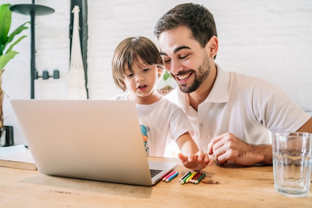 Vater hilft und unterstützt seinen sohn bei der online-schule, während er zu hause bleibt. neues normales lifestyle-konzept.
