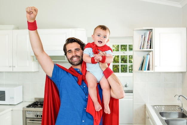 Vater im anhebenden sohn des superheldkostüms in der küche