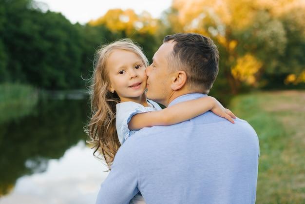 Vater in einem blauen hemd küsst die tochter des mädchens auf die wange