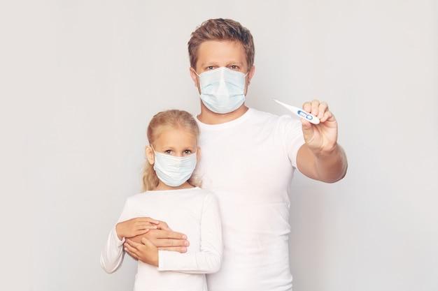 Vater in einer medizinischen maske misst die temperatur seiner tochter mit einem elektronischen thermometer auf einem isolierten hintergrund