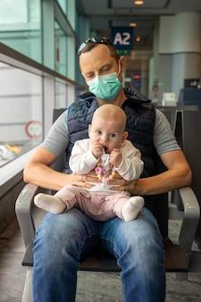 Vater in medizinischer maske und seine tochter warten auf ein einsteigen in ein flugzeug am flughafen