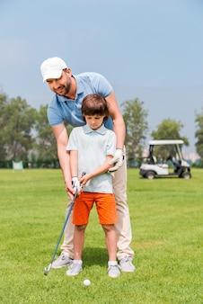 Vater ist immer in der nähe, um mir zu helfen. fröhlicher junger mann, der seinem sohn beibringt, golf zu spielen, während er auf dem golfplatz steht