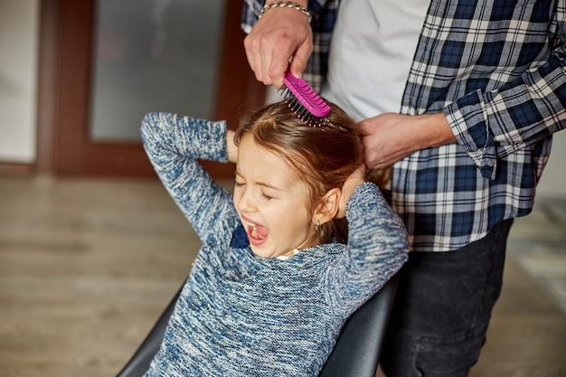Vater kämmt, bürstet seiner tochter zu hause die haare, kind macht grimassen über haareziehen