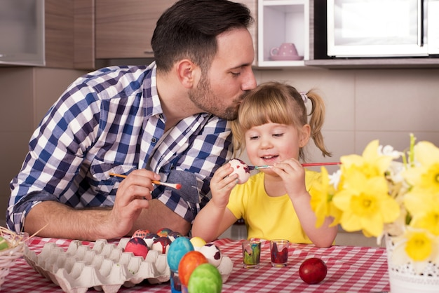 Vater küsst den kopf seines kleinen kindes und bemalt die ostereier